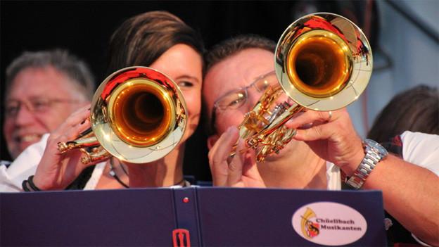 Eine Musikantin und ein Musikantin, die mit einem breiten Lachen Trompete spielen.