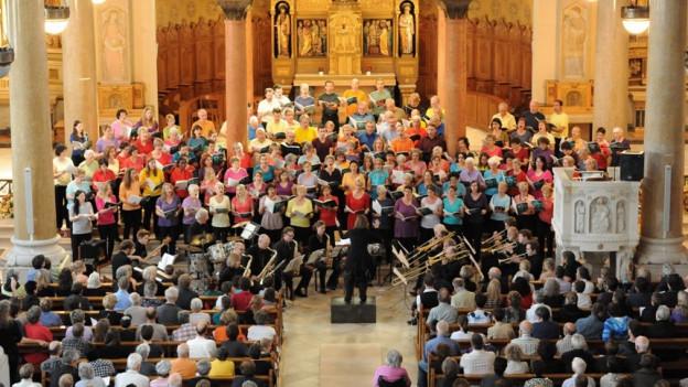 Kirchenschiff voller Sängerinnen, Sänger und Musikanten.