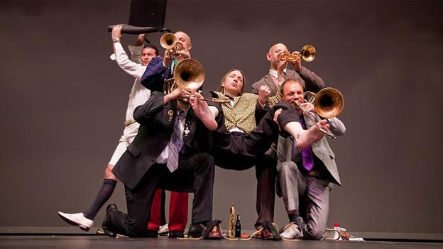 Vier Blasmusikanten halten einen Kollegen an Armen und Beinen, so dass er schwebend getragen wird.