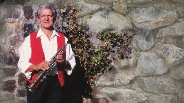 Der Klarinettist steht mit seinem Instrument vor einer Steinmauer.