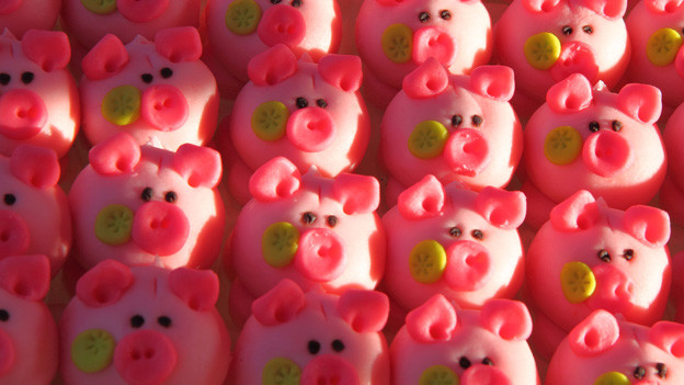 Reihenweise rosarote Schweine aus Marzipan.