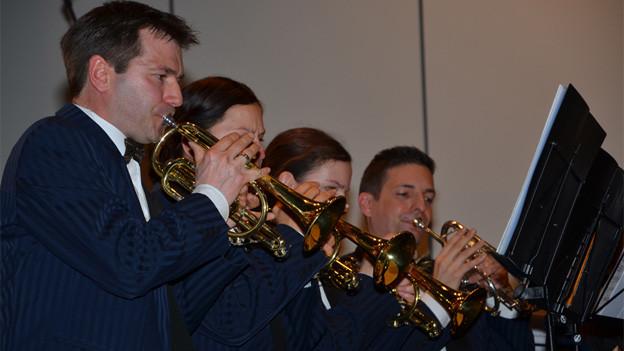 Trompetenspieler- und spielerinnen in dunkelblauen Anzügen, gruppiert vor einem Notenständer.
