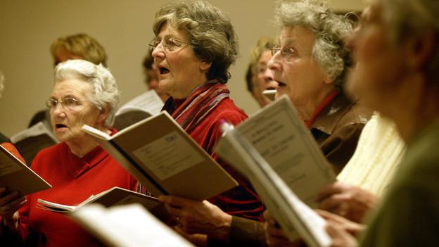 Ältere Frauen mit Notenblättern, stehend und singend im Chor.