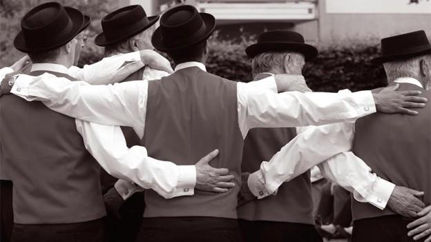 Ein Gruppe Jodler steht im Kreis mit den Händen über der Schulter oder um die Taille des nächsten Kollegen.