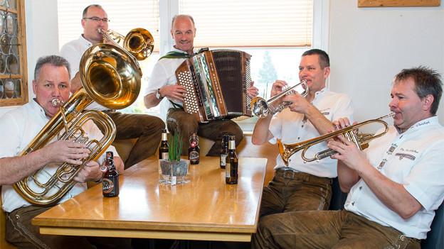 Die fünf Musiker sitzen mit ihren Instrumenten um einen alten Holztisch