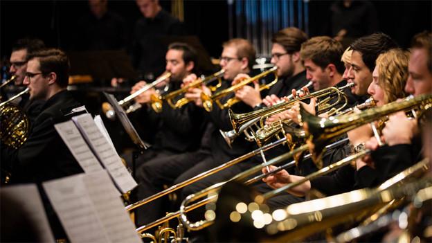Die Blasmusiker in schwarzen Hemden während eines Konzerts.