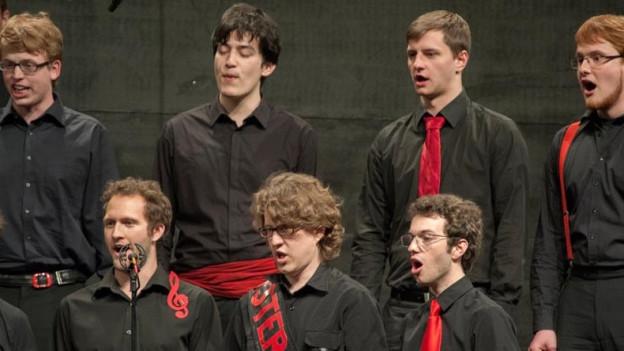 Schweizer Jugendchor in schwarzem outfit mit einzelnen roten Acesoires.