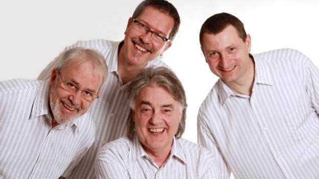Gruppenbild in Weiss mit den vier Musikanten.