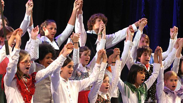 Die jungen Sängerinnen und Sänger strecken beim Singen alle miteinander die Arme in die Höhe.