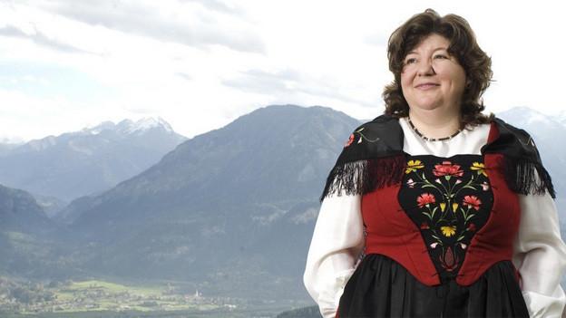 Die Trachtenfrau steht vor einer Bergkulisse mit Blick ins Tal.