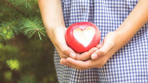 Ein Apfel mit einem herausgeschnittenen Herz in den Händen eines Kindes.