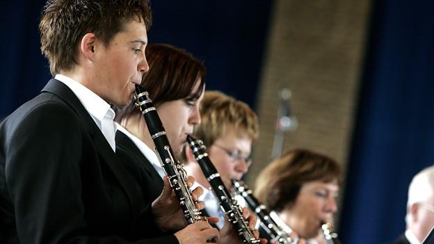 Mehrere Klarinettenspieler vor Notenständern und Mikrofonen.