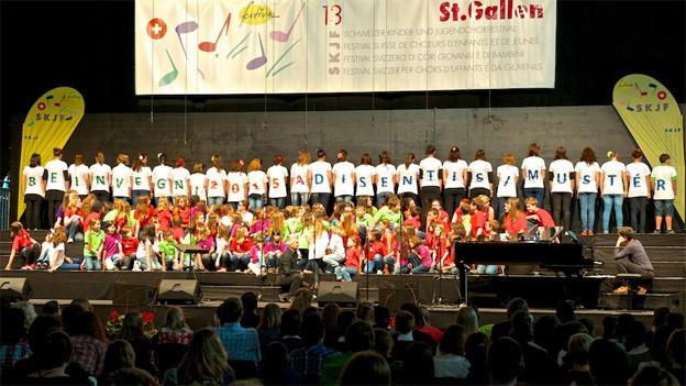 """Eine Gruppe von Kindern steht mit dem Rücken zum Publikum auf der Bühne. Die Buchstaben auf ihren T-Shirts ergeben die Worte «Beinvegni 2015 a Disentis/Mustér""""."""
