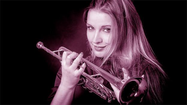 Ein in Magenta-Tönen eingefärbtes Bild einer Trompetenspielerin.