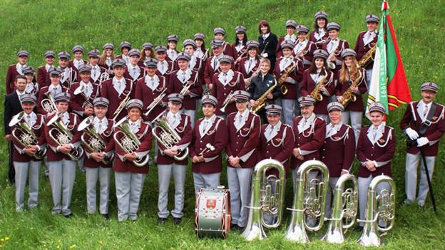 Musikantinnen und Musikanten in weinrot-grauen Uniformen auf einem Gruppenbild.