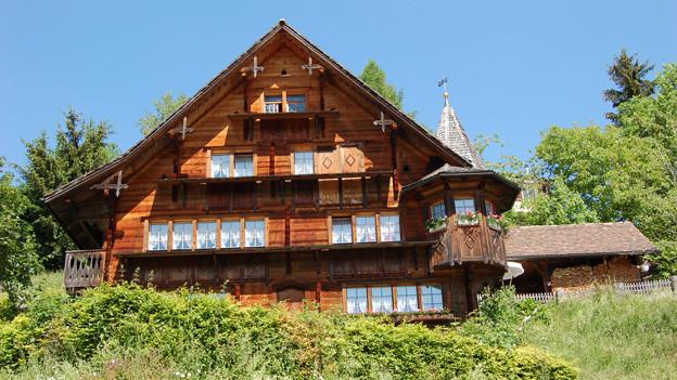 Ein grosses Holzhaus mit vielen kleinen Fenstern.