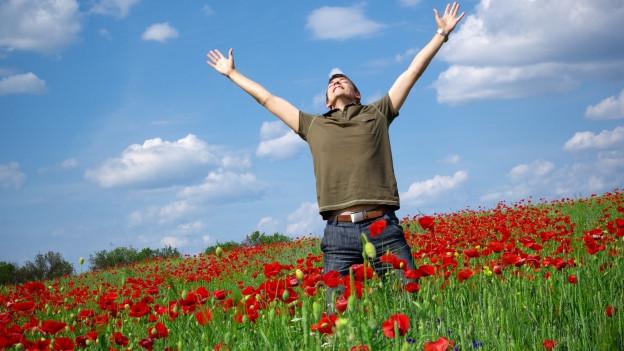 Ein Mann steht auf einem Mohnblumenfeld und streckt beide Arme in die Höhe.