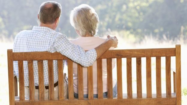Seniorenpaar auf Bank im Sonnenlicht.