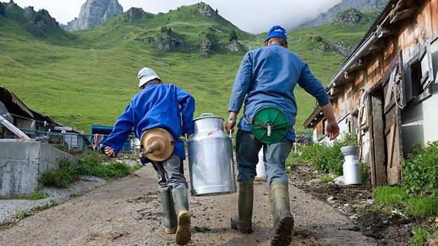 Urnerboden Älpler tragen Milchkanister.