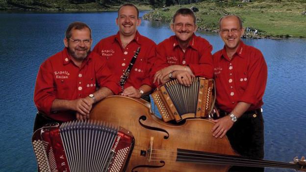 Bildcollage mit vier Musikanten, die mir ihren Instrumenten vor einem klaren Bergsee zu sehen sind.