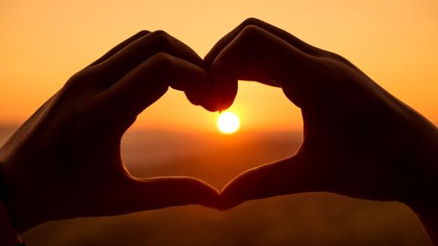 Hände formen Herz vor Sonnenuntergangsstimmung.