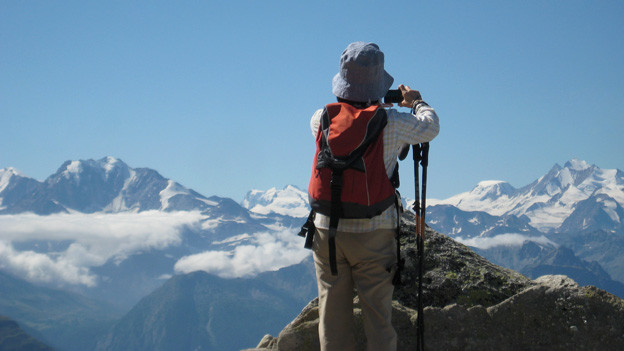 Ein Wanderer schiesst auf der Höhe eines Gipfels ein Foto.