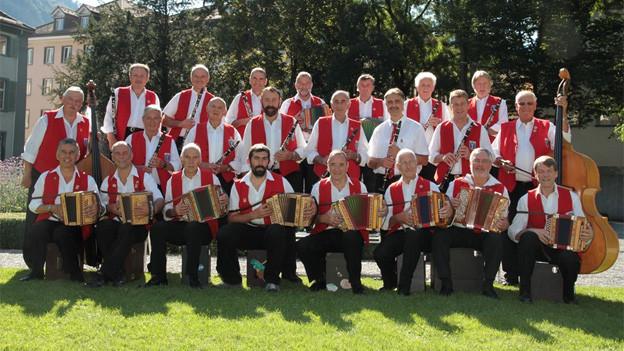 Die Musikanten der grossen Formation tragen alle weisse Hemden und rote Gilets; sie posieren mit ihren Instrumenten fürs Gruppenfoto im Freien.