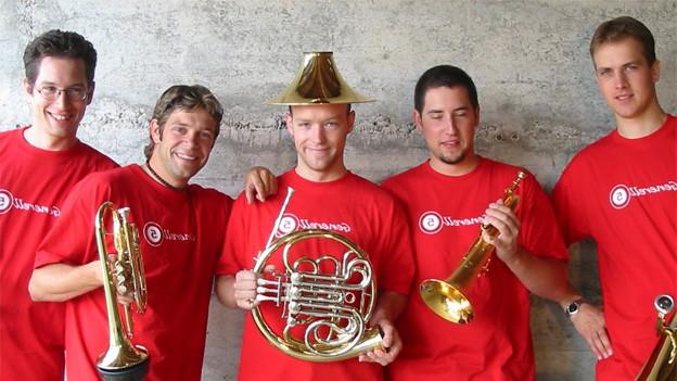 Die fünf Musiker tragen rote T-Shirts und posieren gut gelaunt mit ihren Blechinstrumenten fürs Gruppenfoto.