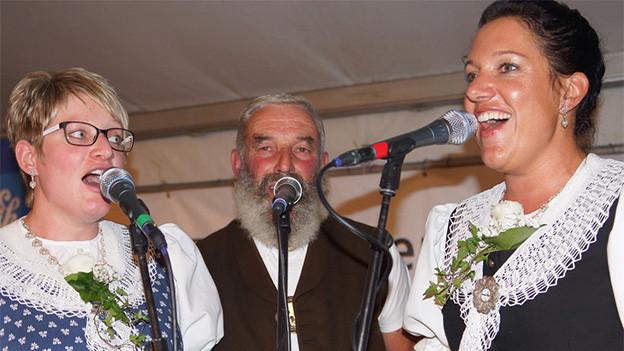 Zwei Jodlerinnen und ein Jodler beim Singen.