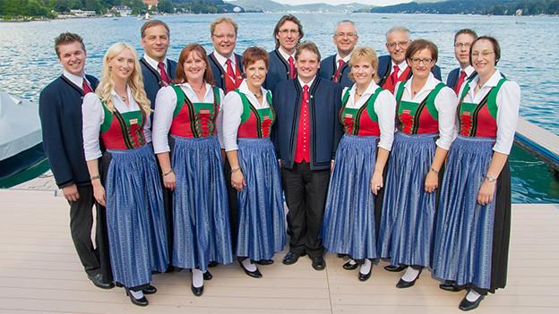 Die Sängerinnen und Sänger stehen am Ufer eines Sees.