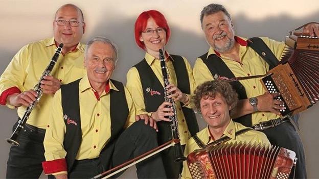 Fünf Musikanten und eine Musikantin mit ihren Instrumenten: zwei Klarinetten, ein Akkordeon, ein Schwyzerörgeli und ein Kontrabass.