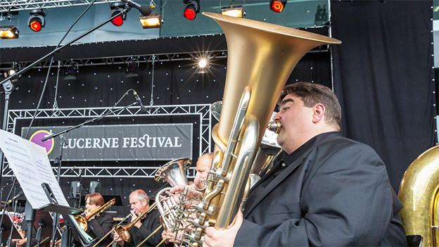 Verschiedene Bläser einer Brassformation während eines Open Air Auftritts auf der Konzertbühne.