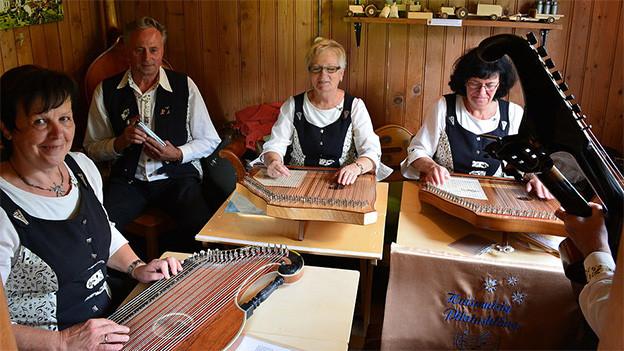 Drei Trachtenfrauen spielen Zither.