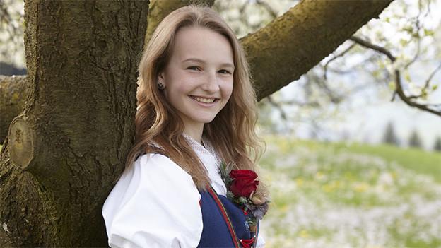 Die junge Jodlerin trägt eine Tracht und lehnt sich an einen Baumstamm.