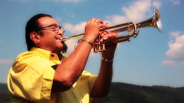 Der Trompeter trägt ein gelbes Hemd und musiziert im Freien.