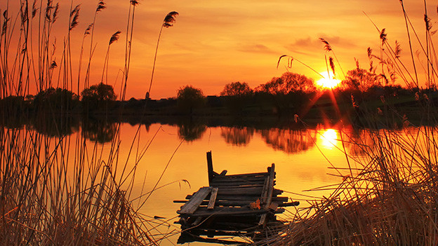Abendstimmung an einem kleinen See, an dessen Horizont die Sonne untergeht.