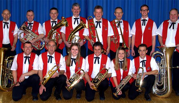 Gruppenfoto mit Musikantinnen und Musikanten, die rote Gilets über weissen Hemden tragen.