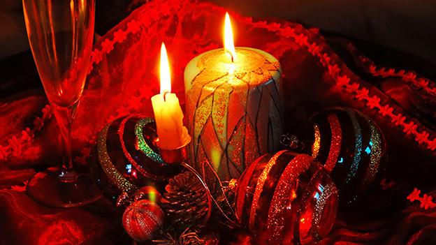 Eine Weihnachtsdekoration mit Kerzen und Weihnachtskugeln in satten Rottönen.