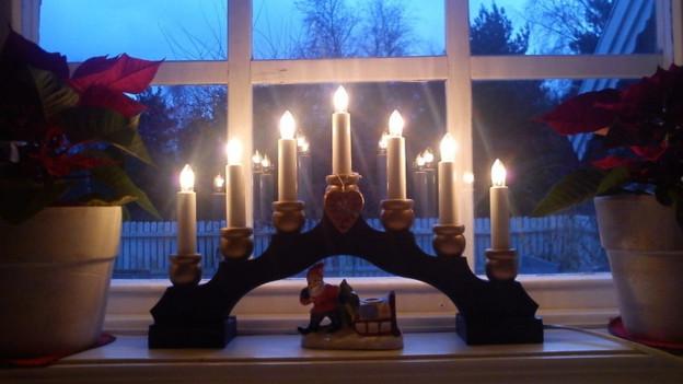 Kerzen-Arrangement vor Fenster.
