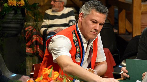 Der Musiker trägt eine rote Jacke einer Appenzellertracht und sitzt an einem Jasstisch.