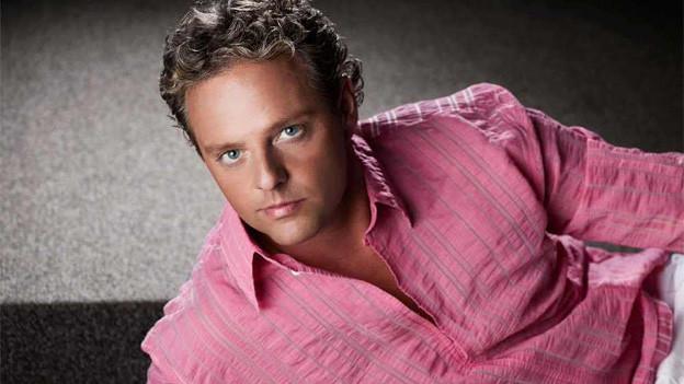 Der blonde Sänger trägt ein rosa Hemd und posiert seitlich liegend fürs Pressefoto.