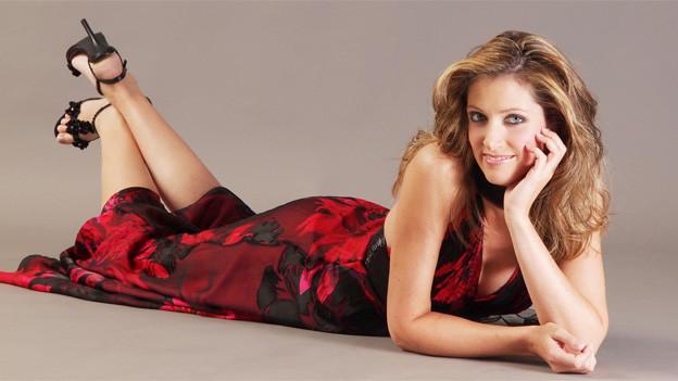 Die Sängerin trägt ein rot-schwarzes, langes Kleid und schwarze Highheels.