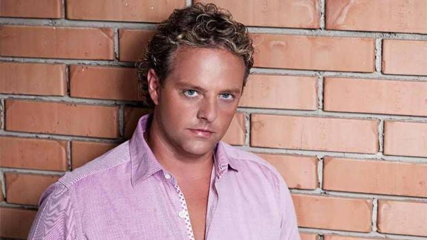 Der blonde Sänger trägt ein rosa Hemd und lehnt an einer roten Backsteinmauer.