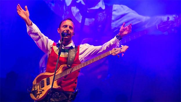 Ein Musiker mit Gitarre und ausgestreckten Armen im Scheinwerferlicht auf der Bühne.