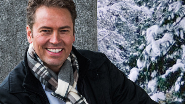 Marcel Schweizer mit Schal und dicker Jacke vor winterlicher Landschaft.
