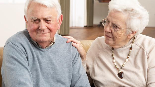 Seniorenpaar. Sie legt ihre Hand tröstend auf seine Schulter.