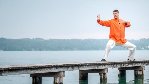 Ein Mann mit weissen Hosen und orangem Hemd zeigt am See auf einem Steg eine Qigong-Übung.