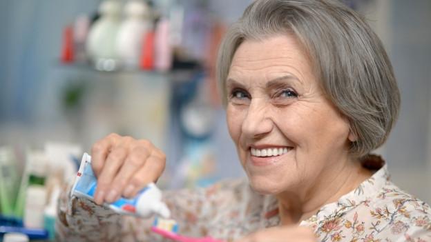 Eine lachende Frau mit grauen Haaren gibt etwas Zahnpasta auf ihre Zahnbürste.