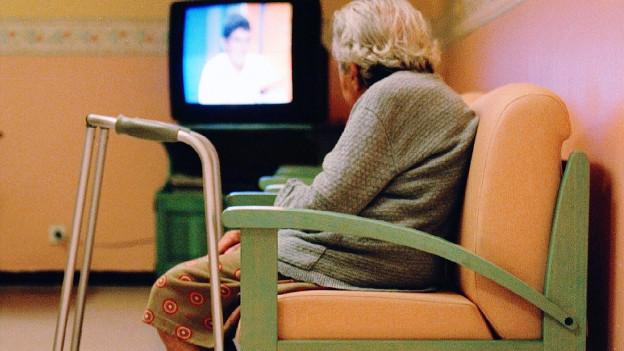 Seniorin sitzt auf hölzerner Bank und betrachtet Fernseher.