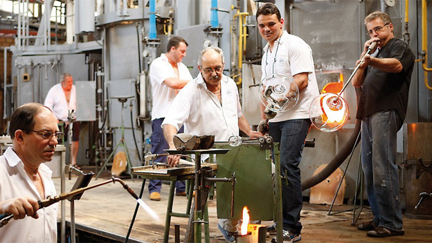 Sechs Männer in weissen Hemden, die Glas bearbeiten.